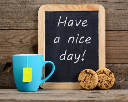 nice day: Cup of tea and small blackboard with Have a nice day! phrase Stock Photo