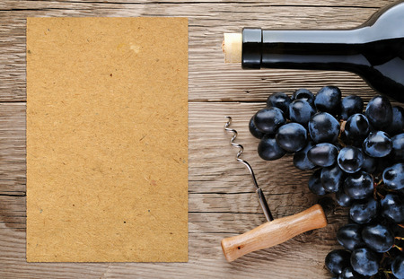 Bottle of wine, corkscrew, grape and blank paper photo