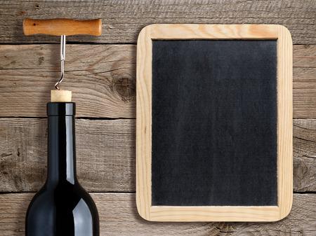 Botella de vino y pizarra en blanco sobre fondo de madera Foto de archivo - 35154624