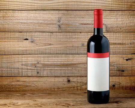 wine bottle label: Bottle of red wine on wooden background