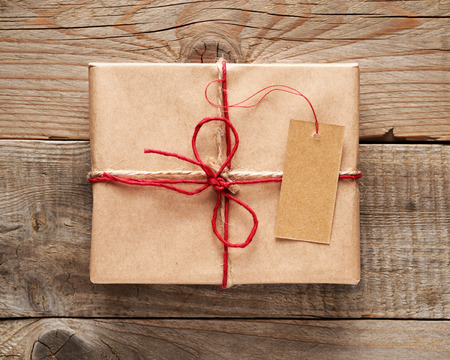 Gift box with tag close-up on wooden background photo