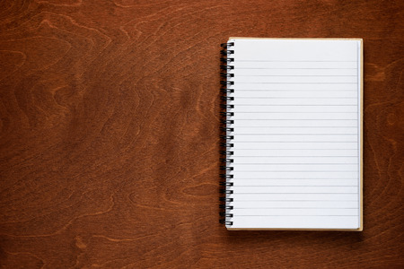 Notepad on wooden background photo