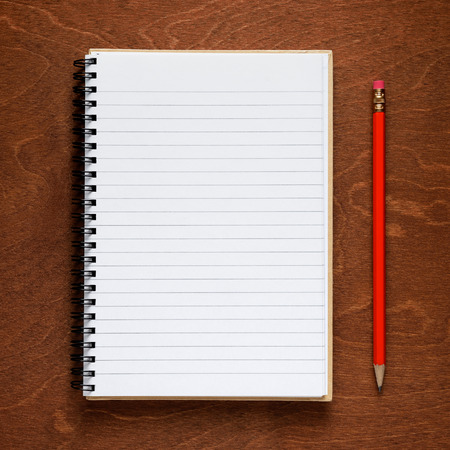 Notepad and pencil on wooden background photo