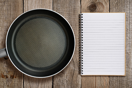 skillet: Frying pan and recipe book on wooden background Stock Photo