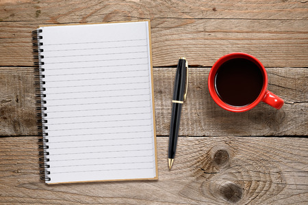 red pen: Coffee cup and notepad with pen on wooden table Stock Photo