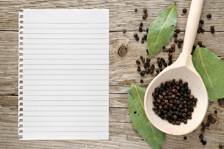 pepe nero: Black pepper and paper for recipe on wooden background Archivio Fotografico