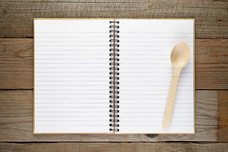 recipe background: Recipe book with spoon on wooden background Stock Photo