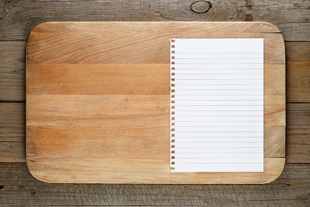 recipe background: Chopping board and paper for recipe on wooden background