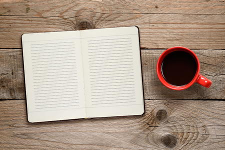diaries: Coffee cup and diary on wooden background