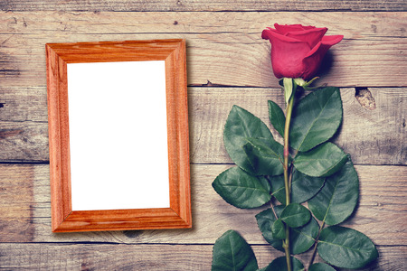 rose photo: Vintage rose and blank photo frame on old wooden background