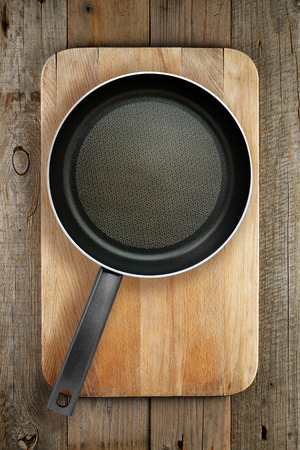 pans: Frying pan on wooden chopping board top view Stock Photo