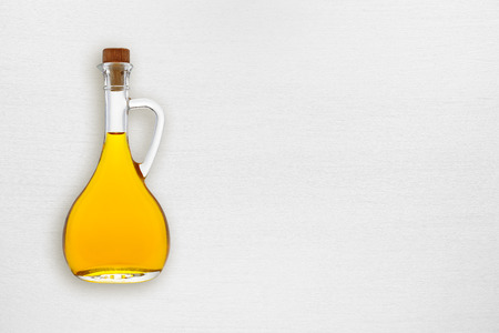 aceite oliva: botella de aceite de oliva en la mesa de madera blanca vista desde arriba Foto de archivo