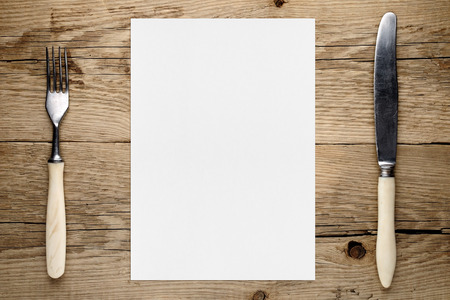 white paper: Blank paper for menu and fork and knife on wooden table