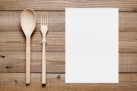 cuchara: Menú en blanco y tenedor y cuchara de madera en la mesa