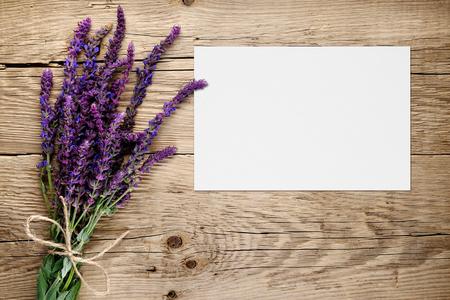 trompo de madera: El manojo de salvia y una tarjeta de felicitación en blanco sobre fondo de madera Foto de archivo