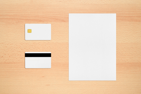 Mock-up of credit card with two sides and paper sheet on office desk Stock Photo