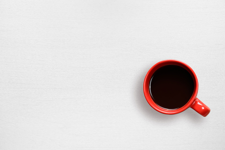 Red coffee cup on white table top view
