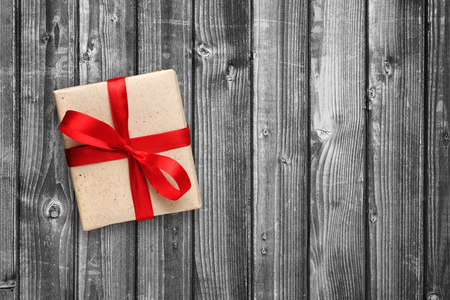 red gift box: Gift box with red ribbon on black and white wooden background