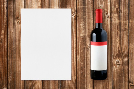 Wine bottle and paper for wine list on wooden background