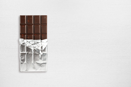 Chocolate bar in foil on wooden table top view Stock Photo