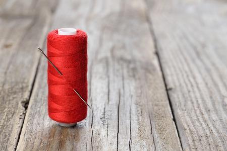hilo rojo: Carrete de hilo de color rojo con la aguja en la mesa de madera