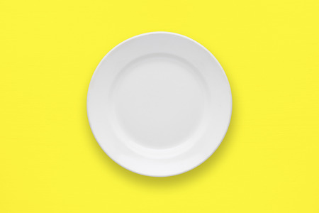 table top: White plate on yellow table top view