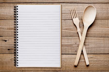Cookbook, forchetta e cucchiaio su tavola di legno Vista dall'alto