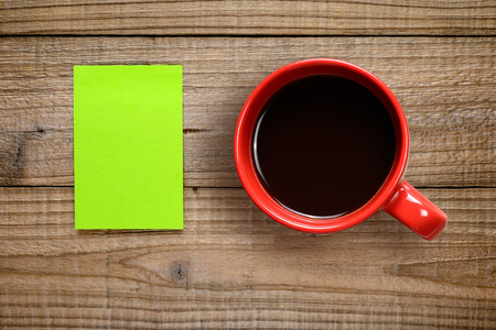postit note: Post-it note and coffee cup on wooden background