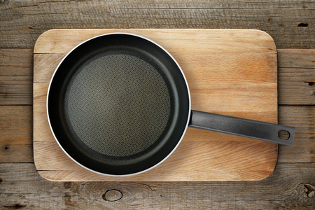 black boards: Empty frying pan on chopping board top view Stock Photo