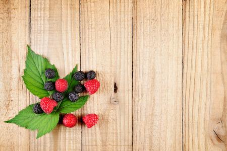black raspberries: Red and black raspberries on wooden background