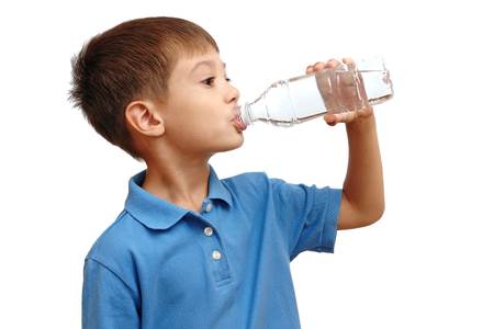 Boy drinks water from bottle isolated on white background photo