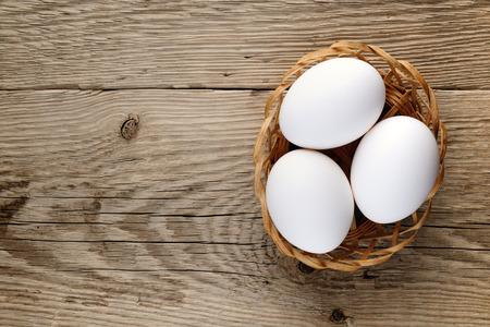 huevo blanco: Huevos en pequeña cesta en la mesa de madera