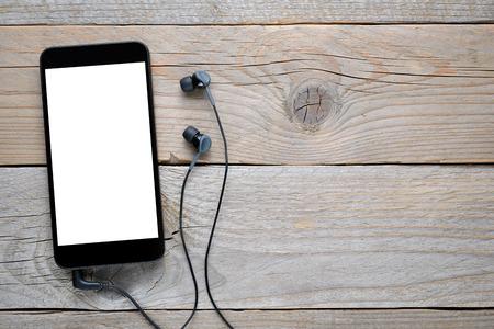 Smartphone met een koptelefoon op houten tafel