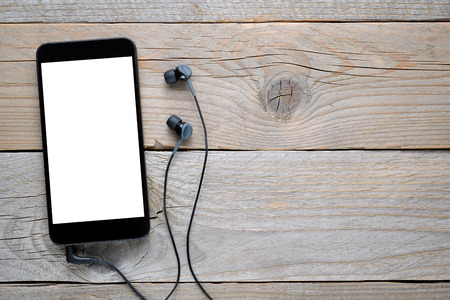 Smartphone with headphones on wooden table