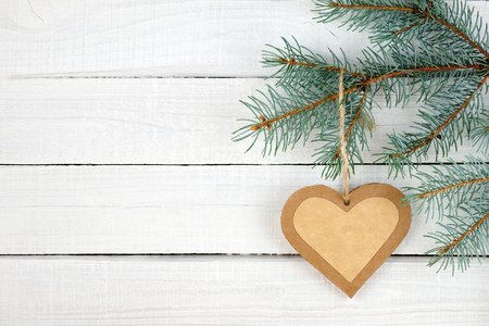 Paper heart and branches of spruce on wooden background Stock Photo