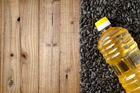 Sunflower seeds and bottle of sunflower oil on wooden background Stock Photo