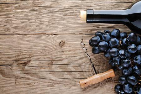 grapes wine: Wine bottle, corkscrew and grape on wooden table top view