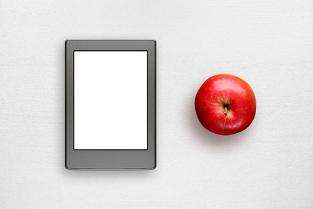 electronic book: Electronic book and apple on white table