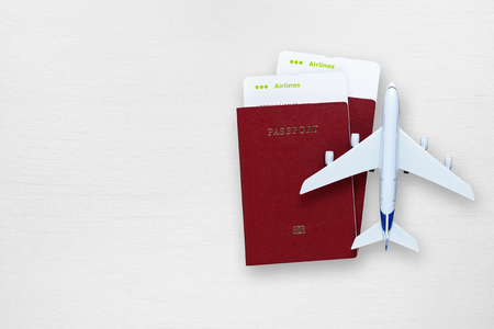 passes: Passports, boarding passes and toy airplane on white table