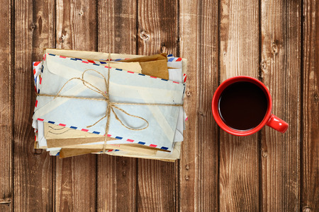 old letters: Pile of old envelopes and coffee cup on wooden table top view