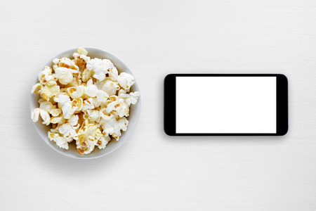 Popcorn and smartphone on white table Stock Photo