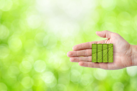 ecological environment: Batteries in hand on green nature background. Ecological energy concept