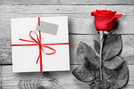 red flower: Red rose and gift box on black and white wooden background Stock Photo
