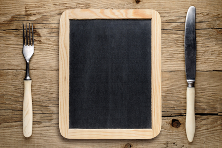 black boards: Blank blackboard, fork and knife on old wooden table