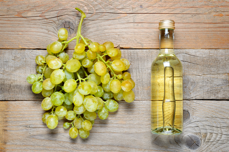 Small bottle of white wine and bunch of grapes on wooden background Stock Photo