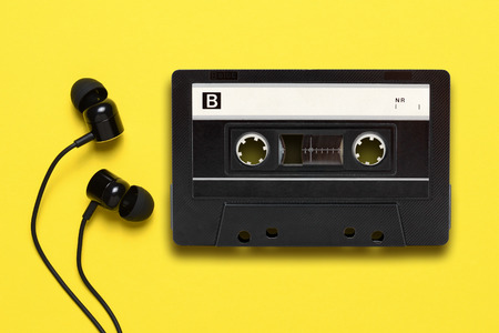 Earphones and audio cassette on yellow background