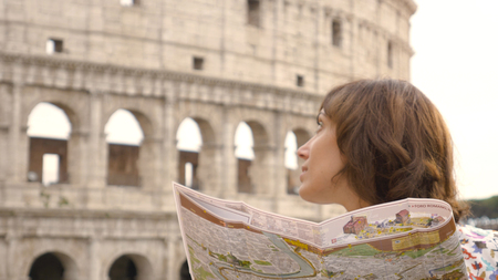 Happy young woman tourist reading a map guide of the city sitting at the table of a bar outside in front of the Colosseum in Rome. Elegant beautiful dress and colorful shopping bags. Stock Photo