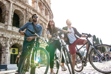 Three happy young friends tourists with bikes and backpacks at Colosseum in Rome having fun. Ground shot with lens flare. Banco de Imagens - 94244717
