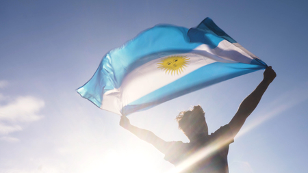 Young man holding argentinian national flag to the sky with two hands at the beach at sunset Stockfoto