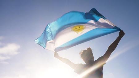 Junger Mann , der argentinischen Nationalflagge zum Himmel mit zwei Händen am Strand bei Sonnenuntergang hält Standard-Bild - 96553812